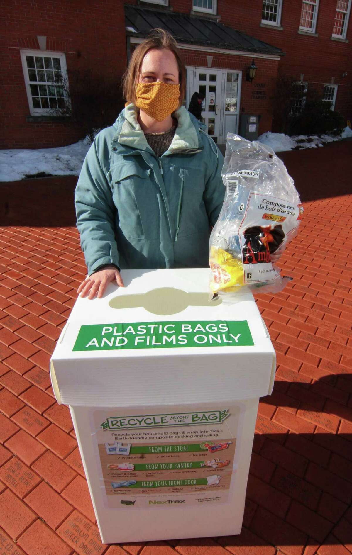 April Lang, with Sustainable Trumbull, poses with one of the group's recycling bins at Trumbull Town Hall in Trumbull, Conn., on Saturday Feb. 6, 2020. Lang is coordinating a recycling challenge to get plastic bags out of landfills and prevent them from becoming litter.
