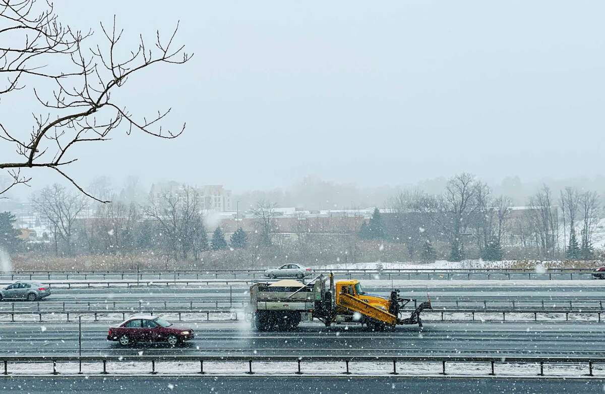 A snowplow spreads ice melt as the driver heads north on Interstate 87 on Sunday, February 7, 2021, in Latham, N.Y. (Paul Buckowski/Times Union)