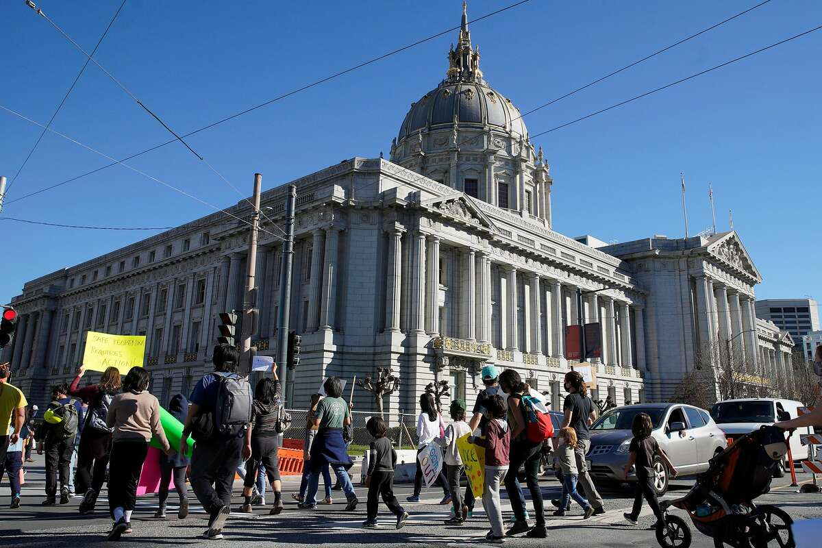 Hundreds of people march to City Hall after a rally at the SFUSD building, Saturday, Feb. 6, 2021, in San Francisco, Calif. People protested against remote education and demanded schools to reopen in-person education.