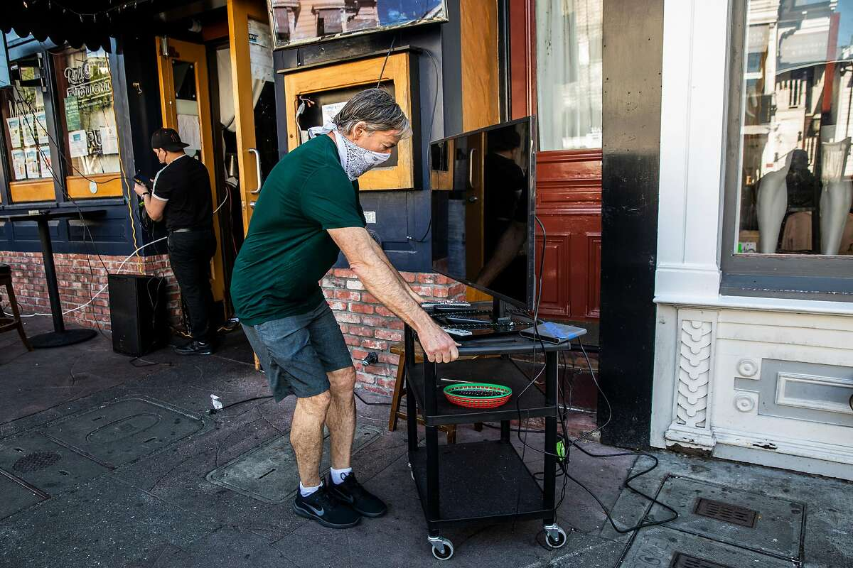 Johnny Metheny, owner of the Blue Light on Union Street, pulls a television into position in anticipation of customers coming to watch Super Bowl LV outdoors in San Francisco.