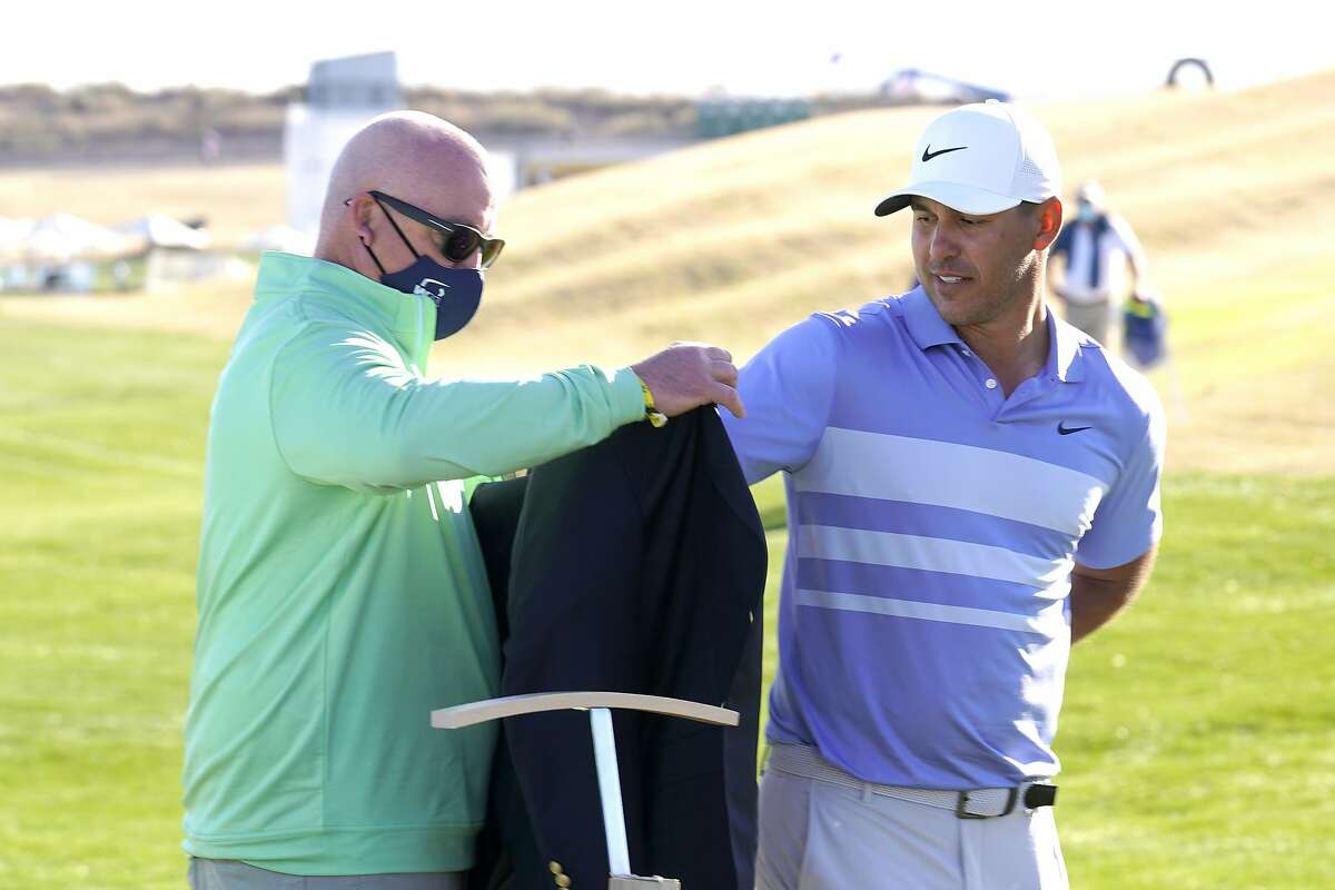 Brooks Koepka receives the winner's jacket at the Phoenix Open for the second time. He got $1.314 million for his work.