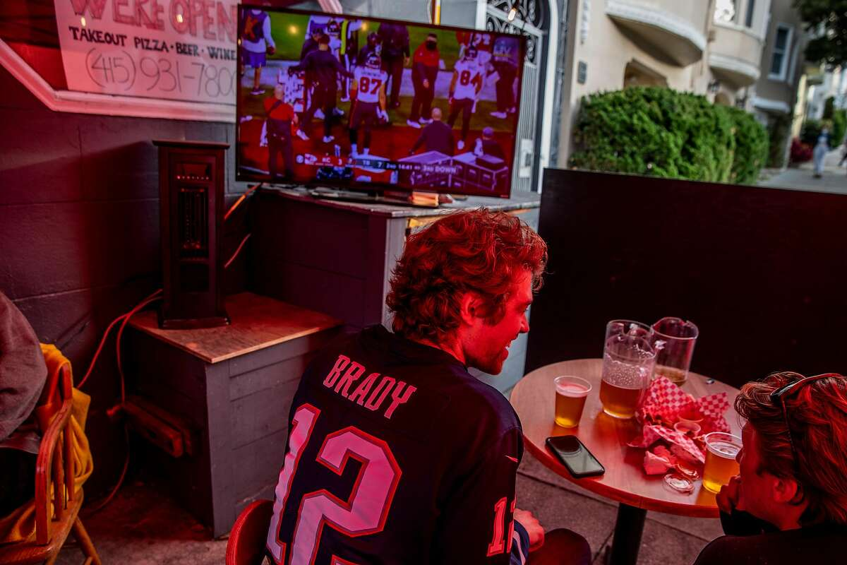 Ted Patsos shows his colors as he watches Super Bowl LV in an outdoor area at Final Final in San Francisco.