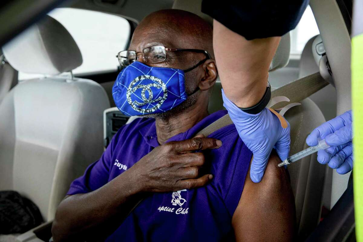 Pastor Johnny Guyton receives his first dose of the Moderna coronavirus vaccination on Jan. 29 at a drive-thru line at the Alamodome, organized by the San Antonio Fire Department.