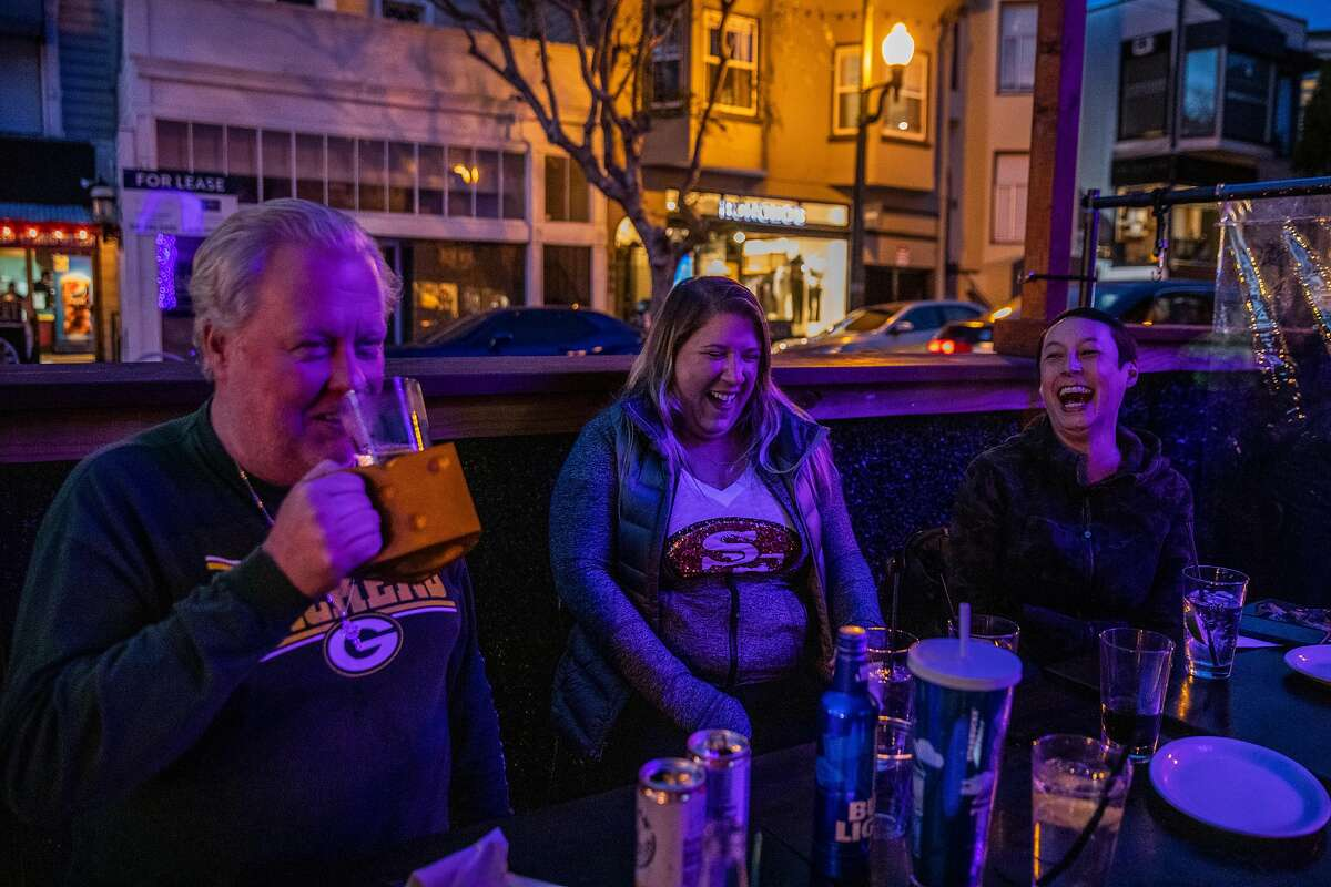 Friends J.J. Dillion, Suzie Schornack and Chris Lebar, at the Blue Light on San Francisco's Union Street, are among the partiers on a strictly outdoor Super Bowl Sunday.