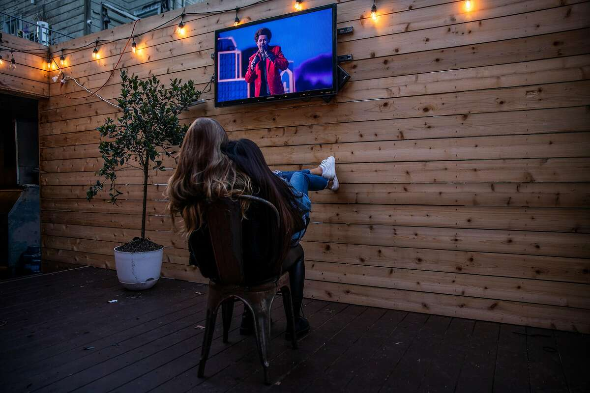 Adeline Bertola, left, and Aly Velazquez watch the Super Bowl LV halftime show at The Blue Light in San Francisco, California on Sunday, Feb. 7, 2021.
