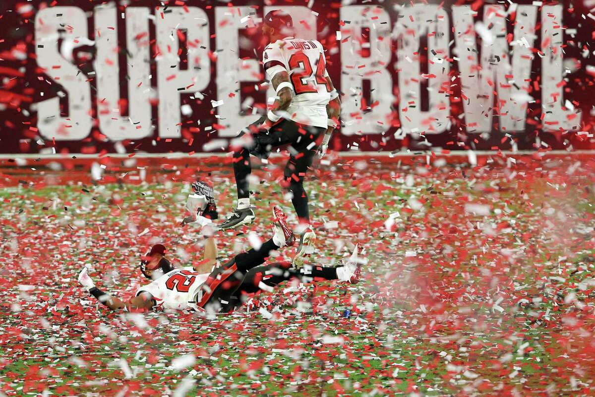 TAMPA, FLORIDA - FEBRUARY 07: Andrew Adams #26 and Carlton Davis #24 of the Tampa Bay Buccaneers celebrate as confetti falls after defeating the Kansas City Chiefs in Super Bowl LV at Raymond James Stadium on February 07, 2021 in Tampa, Florida. The Buccaneers defeated the Chiefs 31-9. (Photo by Patrick Smith/Getty Images)