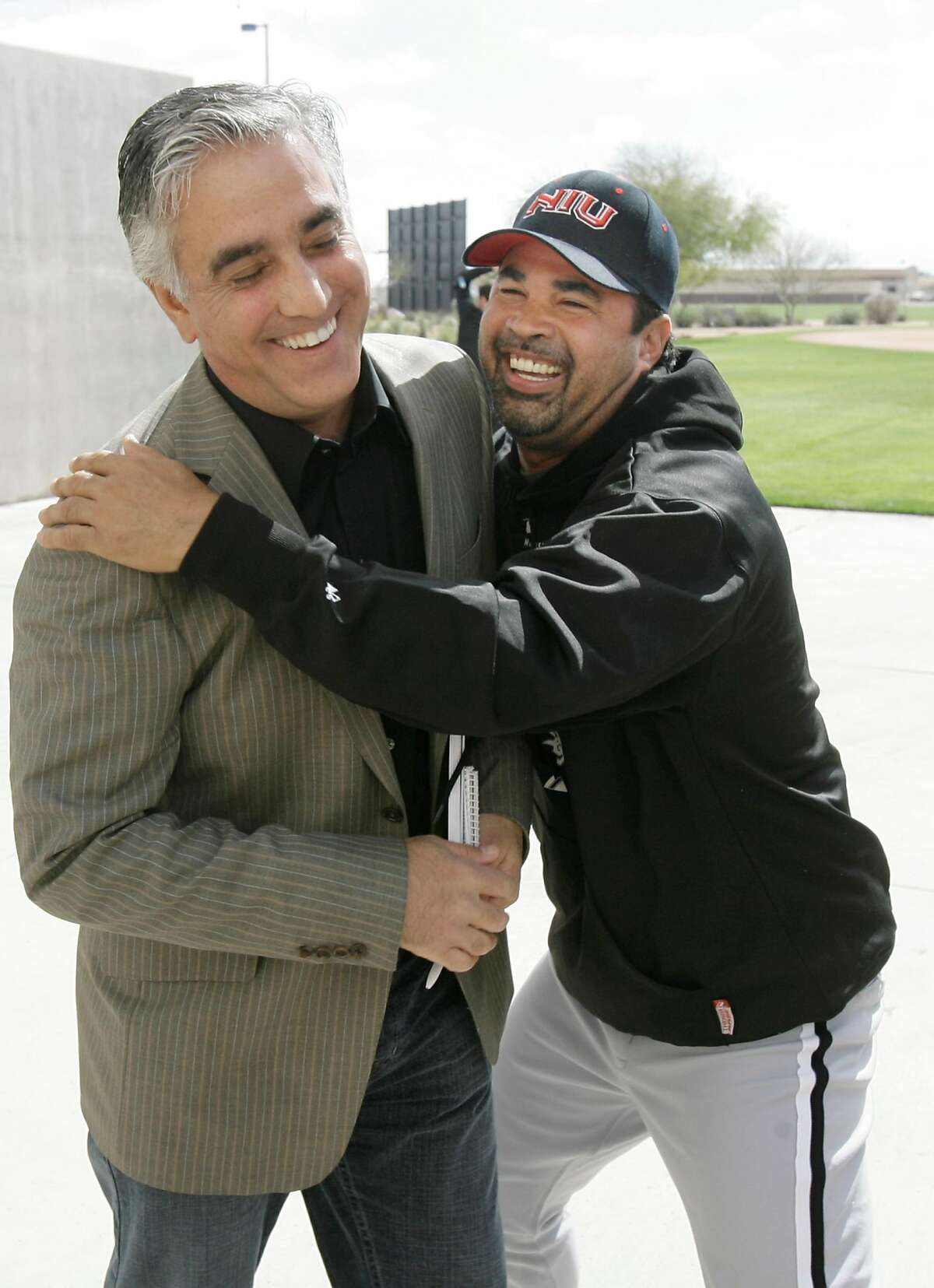 Chicago White Sox' manager Ozzie Guillen jokes with ESPN's Pedro Gomez after a news conference during pitchers and catchers first day of baseball spring training Saturday, Feb. 16, 2008, in Tucson, Az.  (AP Photo/M. Spencer Green)