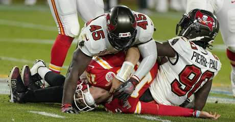 Kansas City Chiefs quarterback Patrick Mahomes, center, is tackled by Tampa Bay Buccaneers inside linebacker Devin White (45) and outside linebacker Jason Pierre-Paul, right, during the second half of the NFL Super Bowl 55 football game Sunday, Feb. 7, 2021, in Tampa, Fla. (AP Photo/Gregory Bull)