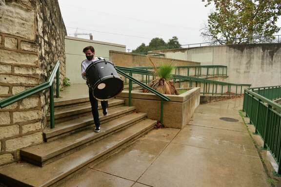 James Gemino, a New York native who recently moved to San Antonio, carries a drum kit down the steps near the Josephine Street bridge on a rainy Sunday afternoon.
