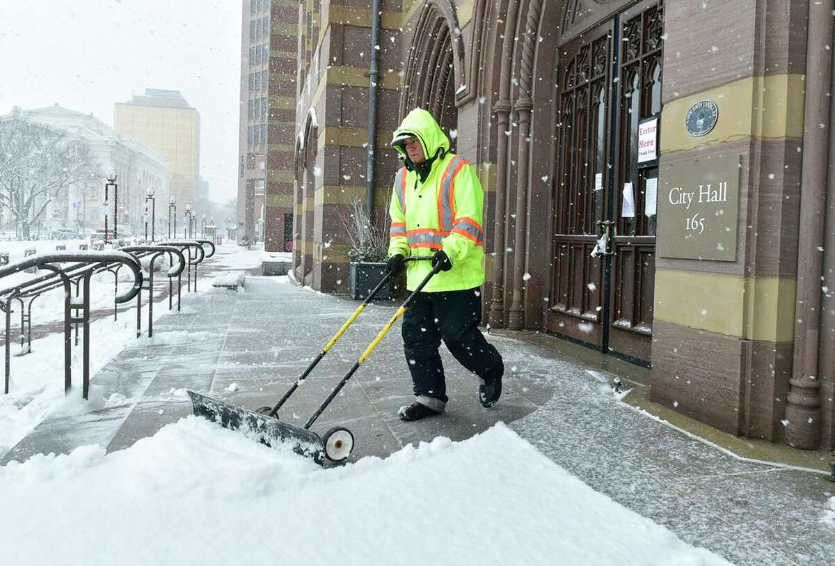 New Haven, Connecticut - Sunday, February 07, 2021: Vidal Santos, and employee of Perco Inc., a landscaping management company, clears snow Sunday from the steps of New Haven City Hall.