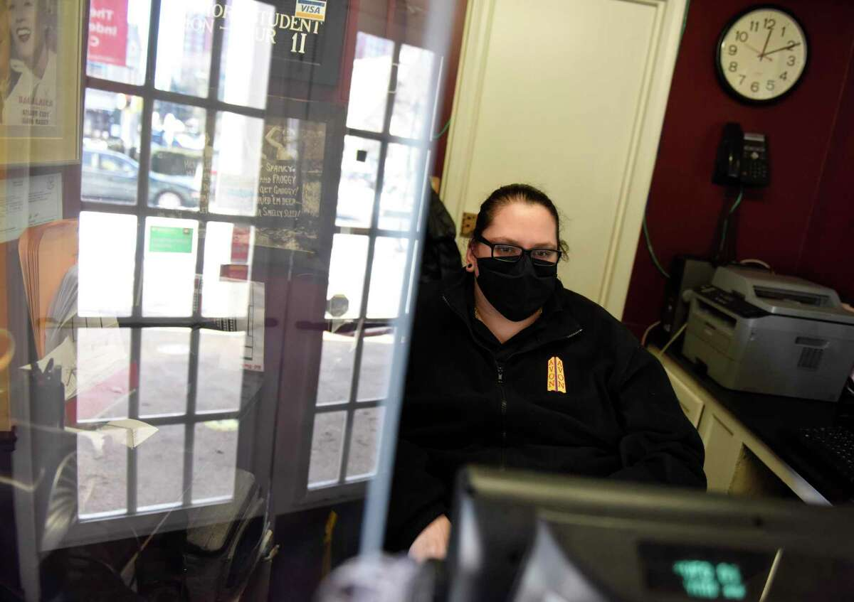 Theatre Manager Ashley Vanderwaren works behind plexiglass at the ticket counter at the Avon Theatre in Stamford, Conn. Thursday, Feb. 4, 2021. The theater has re-opened with required masks and social distancing as well as safety measures including operating at 40 percent capacity, every other row off limits, a new HEPA air filter, and plexiglass at all counters.