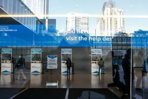 The check-in kiosks are seen through a window at the mass vaccination site opened today at San Francisco's Moscone Convention Center to healthcare workers and people over 65 on February 5, 2021 in San Francisco, California. (Photo by Amy Osborne / AFP) (Photo by AMY OSBORNE/AFP via Getty Images)