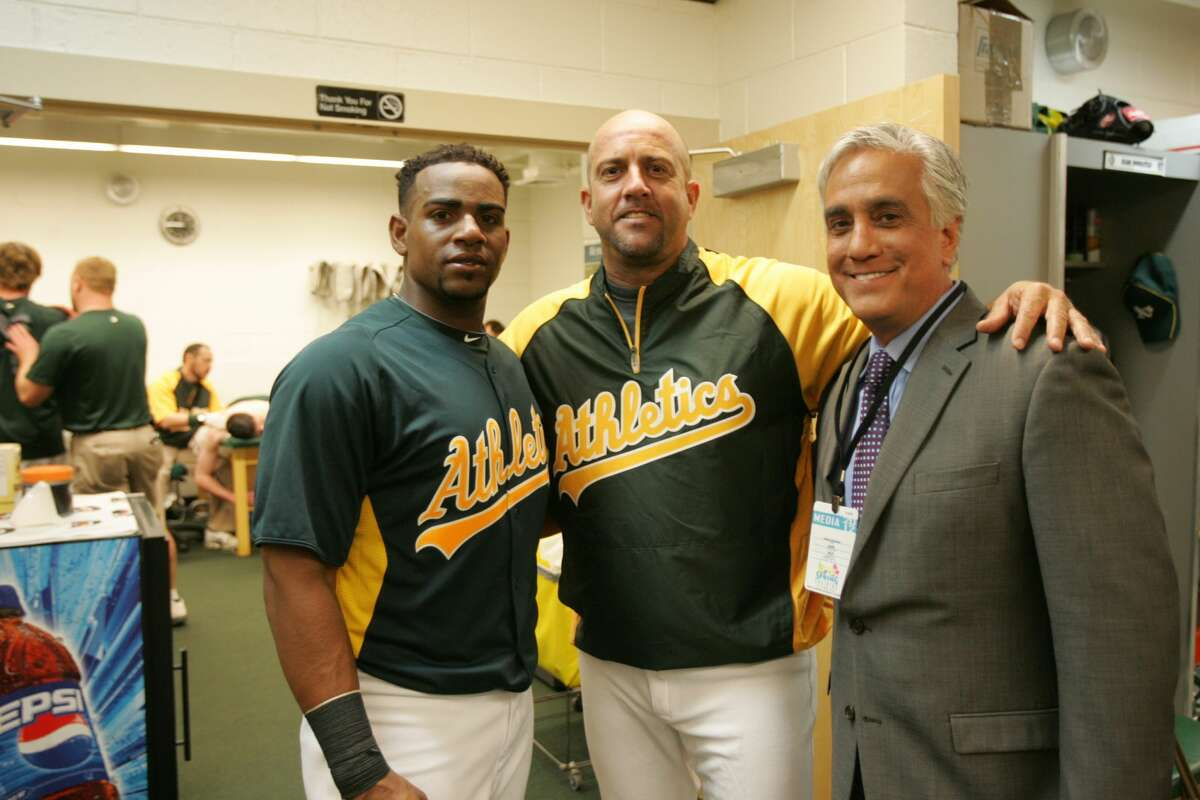 Yoenis Cespedes and Ariel Prieto of the Oakland Athletics talk with Pedro Gomez of ESPN in the clubhouse following a spring training game March 5, 2012.