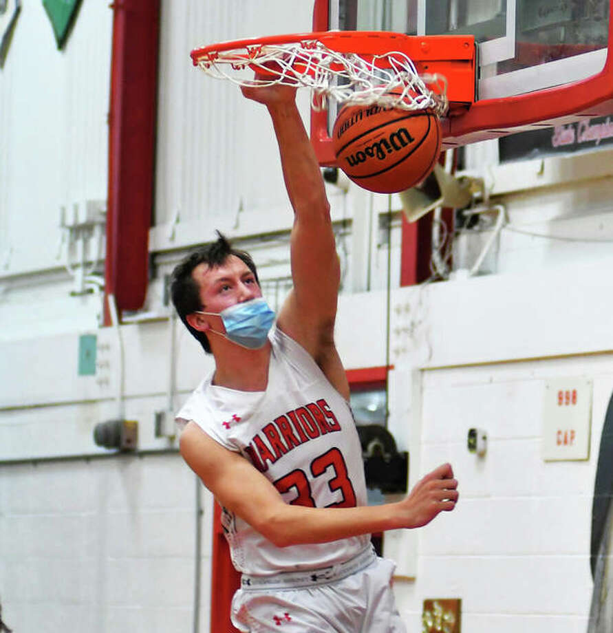 Calhoun senior Corey Nelson throws down a dunk that would provide his last points for Warriors basketball. When Nelson landed, he suffered a torn ACL and torn meniscus in his knee Wednesday at Ringhausen Gym in Hardin. Photo: Bonnie Snyders / For The Telegraph