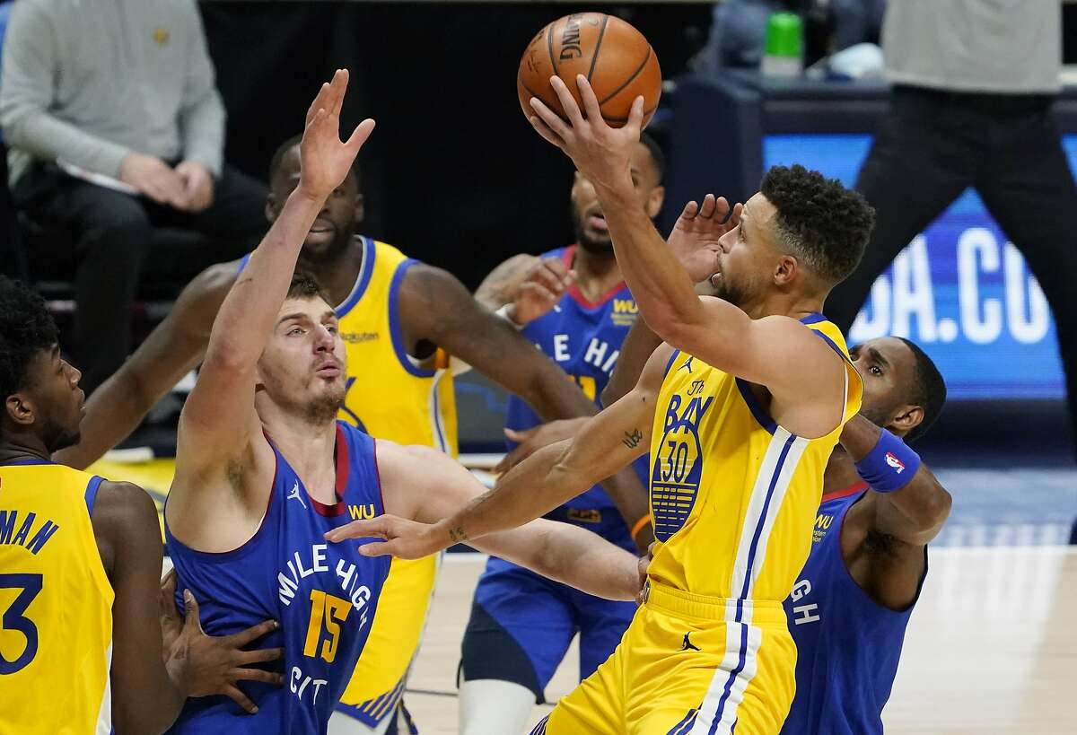 Golden State Warriors guard Stephen Curry, front right, drives as Denver Nuggets center Nikola Jokic defends during the second half of an NBA basketball game Thursday, Jan. 14, 2021, in Denver. The Nuggets won 114-104. (AP Photo/David Zalubowski)