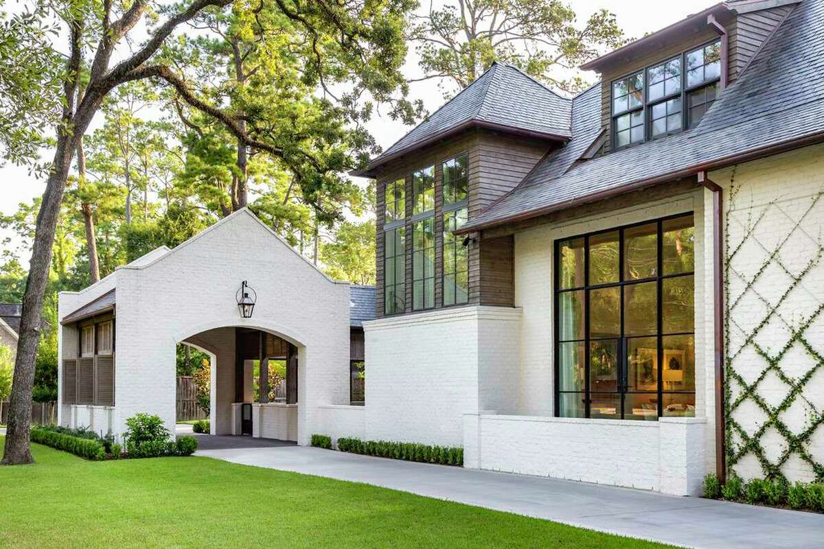 This Houston home built by Thompson Custom Homes was built with a painted brick exterior. Its white brick is complemented by Cypress siding stained gray and steel-framed windows and doors.