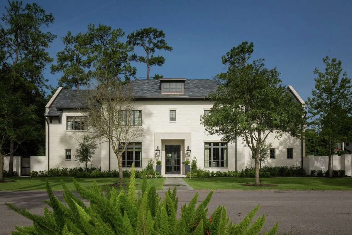 This Houston home built by Thompson Custom Homes was built with a painted brick exterior. Its brick was painted white and paired with a dark roof and steel-framed windows and doors.