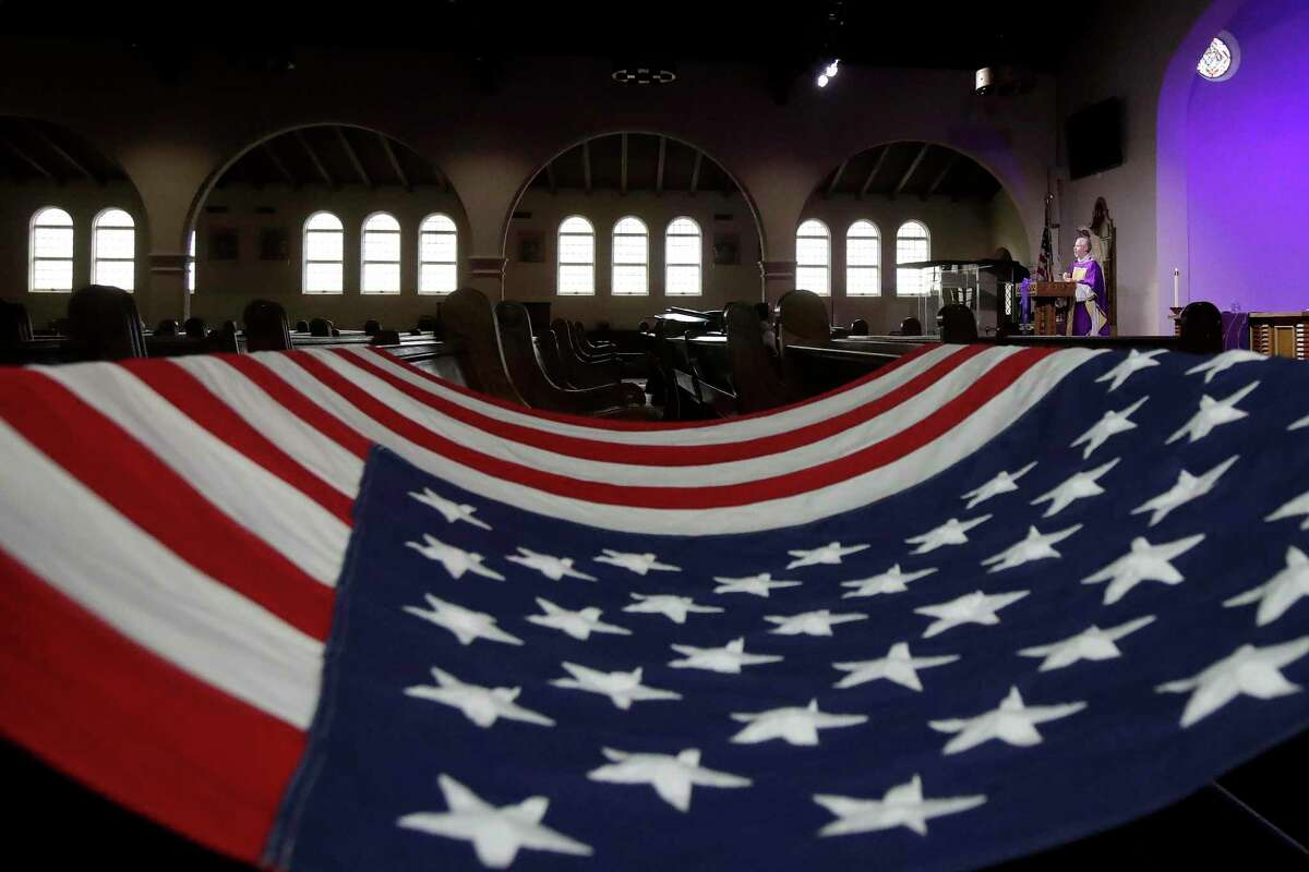 A U.S. flag is draped over pews as the Rev. Roger Gustafson, right, is recorded celebrating Mass in an empty St. Brendan the Navigator Catholic Church in San Francisco on March 28, 2020.
