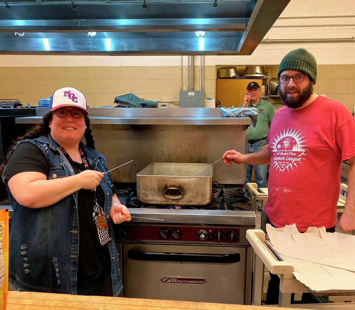In this file photo, Aisha Newenhouse and Joe Korzeniewski are shown getting the oil ready to fry another batch ofpaczki fortheManistee Catholic Central Athletic Association's paczki fundraiser last year. (File photo)