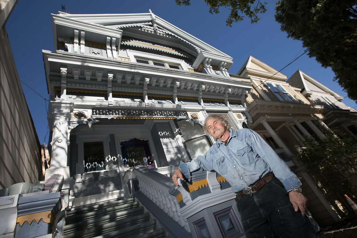 Skeeter Jones poses in front of one of Victorian homes he restored in San Francisco on Feb. 5, 2021. For more than 40 years, Jones has specialized in restoring the facades of old Victorian homes.