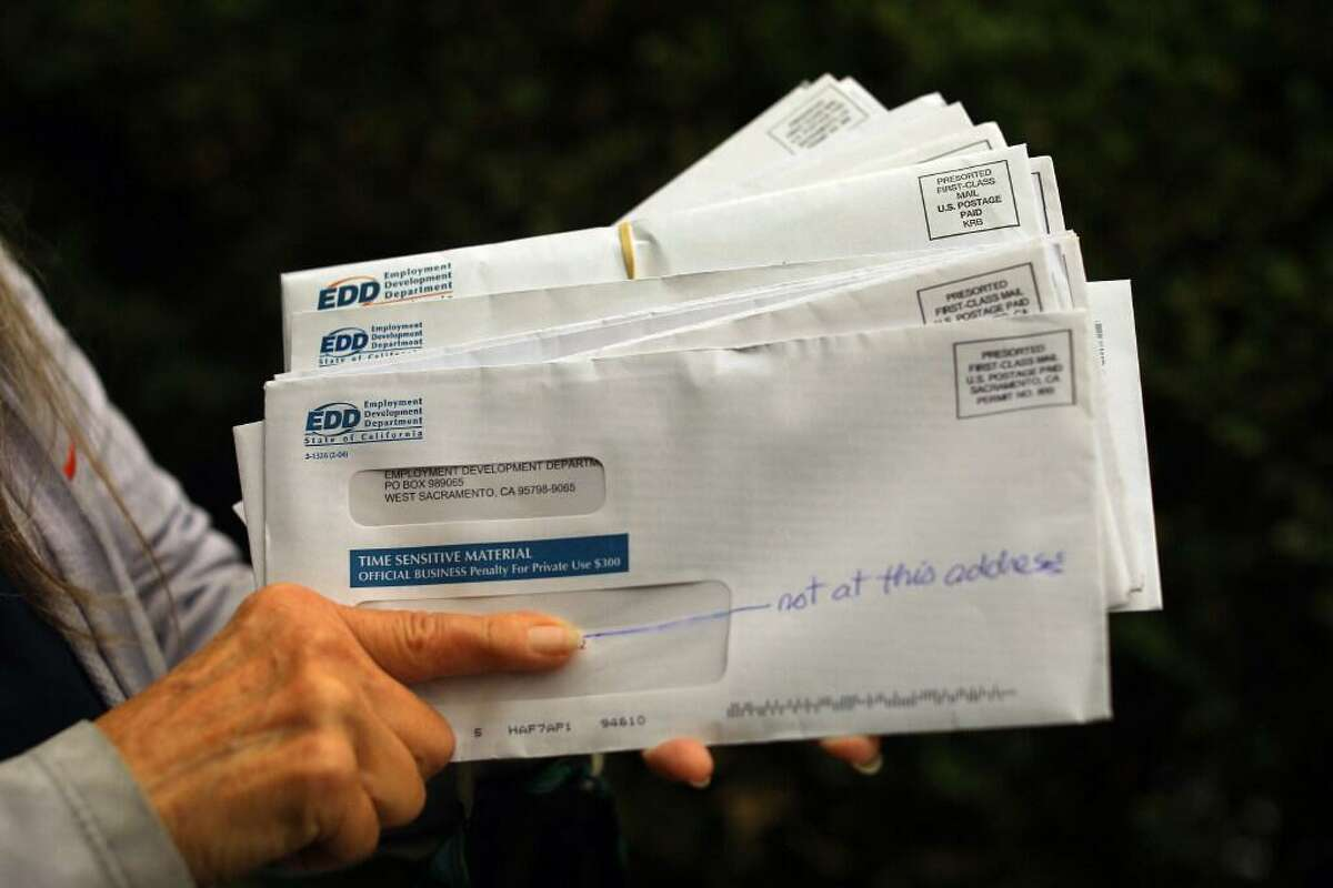 A California resident holds mail that was received at her home address by people who presumably attempted to defraud the California Employment Development Department, in Oakland, Calif., Sept. 10, 2020. A rash of fraudulent pandemic unemployment claims filed under the names of jail and prison inmates, including more than 100 on death row, has bilked California out of hundreds of millions of dollars, a law enforcement task force said Tuesday, Nov. 24.