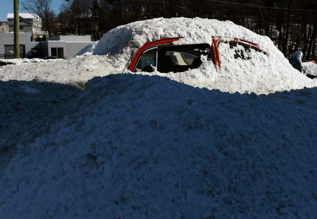 A pile of snow covers a Volkswagen Beetle in front of the Freccia Brothers dealership in Greenwich, Conn. Monday, Feb. 8, 2021.