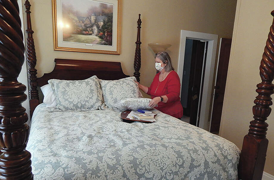 Owner Gwen Eyer does some tidying at Blessings on State bed and breakfast. While the hospitality industry has been hard hit during the past year, there are glimmers of hope that travel could begin to pick up. Photo: Angela Bauer   Journal-Courier