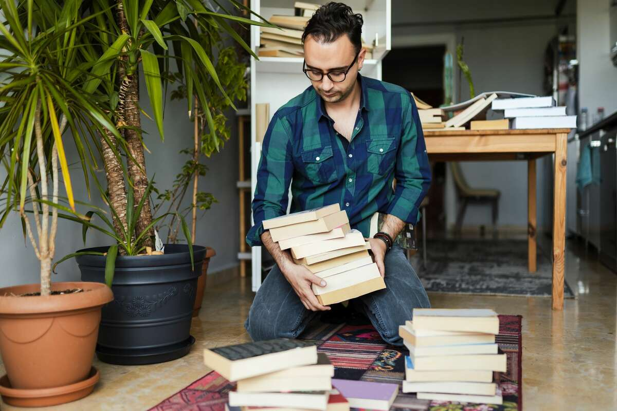 Millennial man organizing his book collections