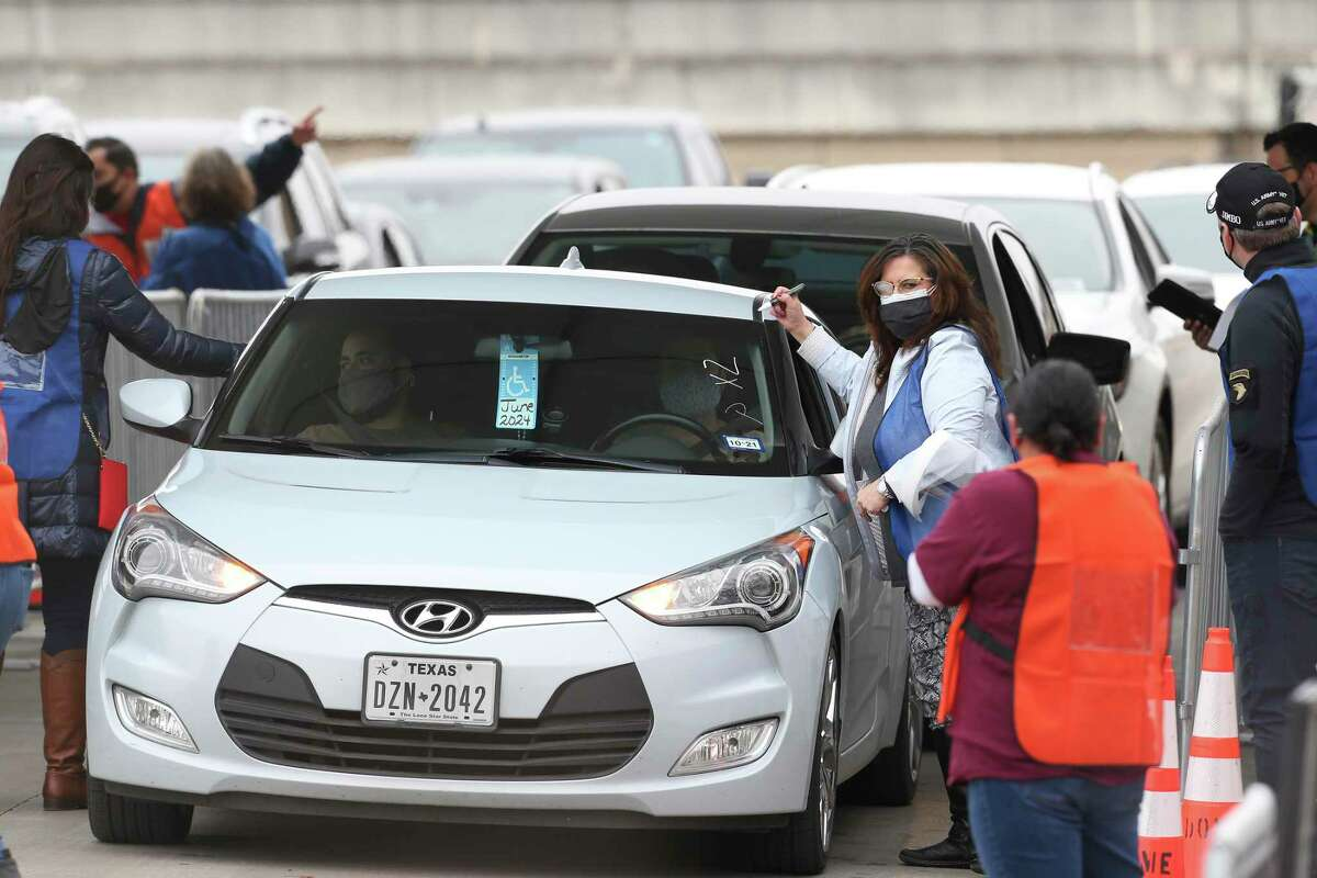 Vehicles enter the Alamodome parking lot for COVID-19 vaccinations on Jan. 20, 2021. It is one of several sites where people with an appointment can get a free vaccine.