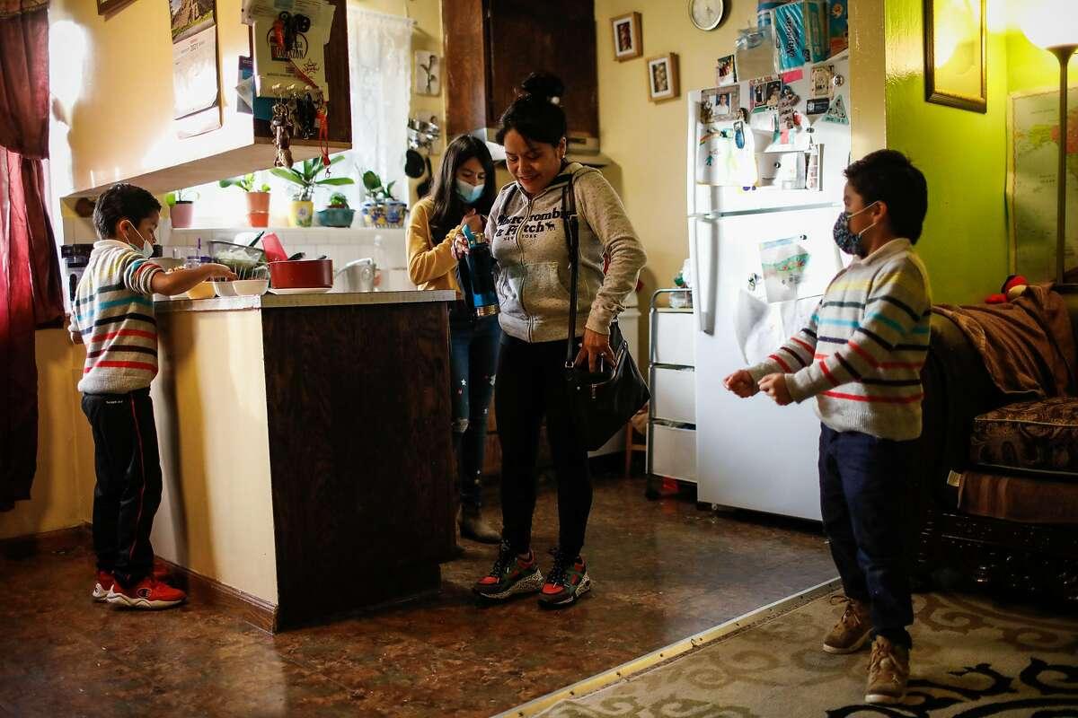 Minerva Pacheco (center) and her children Daniel Martinez Pacheco, 8, (left), Iris Martinez Pacheco, 11 and Brian Martinez Pacheco, 7 (right) prepare to go to the park on Monday, Feb. 8, 2021 in San Francisco, California.