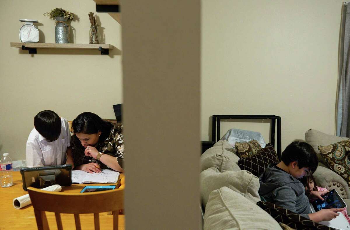 Vanessa Rodriguez, center, helps her 9-year-old son Giovanny, left, with math home work as her two other children play with a tablet in their living room Wednesday, Feb. 3, 2021, in Crosby, Texas. Rodriguez, from Mexico, has been thinking about applying for DACA for many years, but it wasn't until president Joe Biden took office that she finally felt safe to do so. As a mother of three American children, she was afraid of giving her information to the government and being deported. Now she and her husband are among the many DACA eligible people that are applying for the first time.