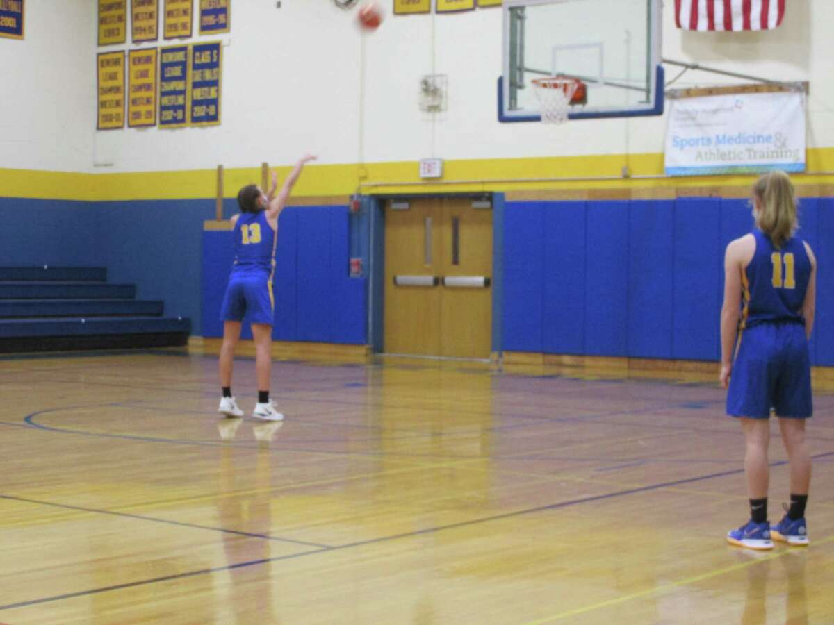 High scorer Sydney Segalla shoots a foul shot in Housatonic's opening-day win at The Gilbert School while teammate Tori Dodge looks on from a distance - a Covid protocol for the first shot of a two-shot foul.