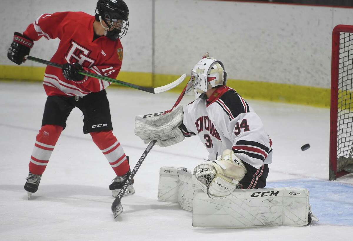 Fairfield Prep's Aaron Wong deflects a shot past New Canaan goalie Beau Johnson in the second period of their opening game of the FCIAC ice hockey season at the Darien Ice House in Darien, Conn. on Monday, February 8, 2021.