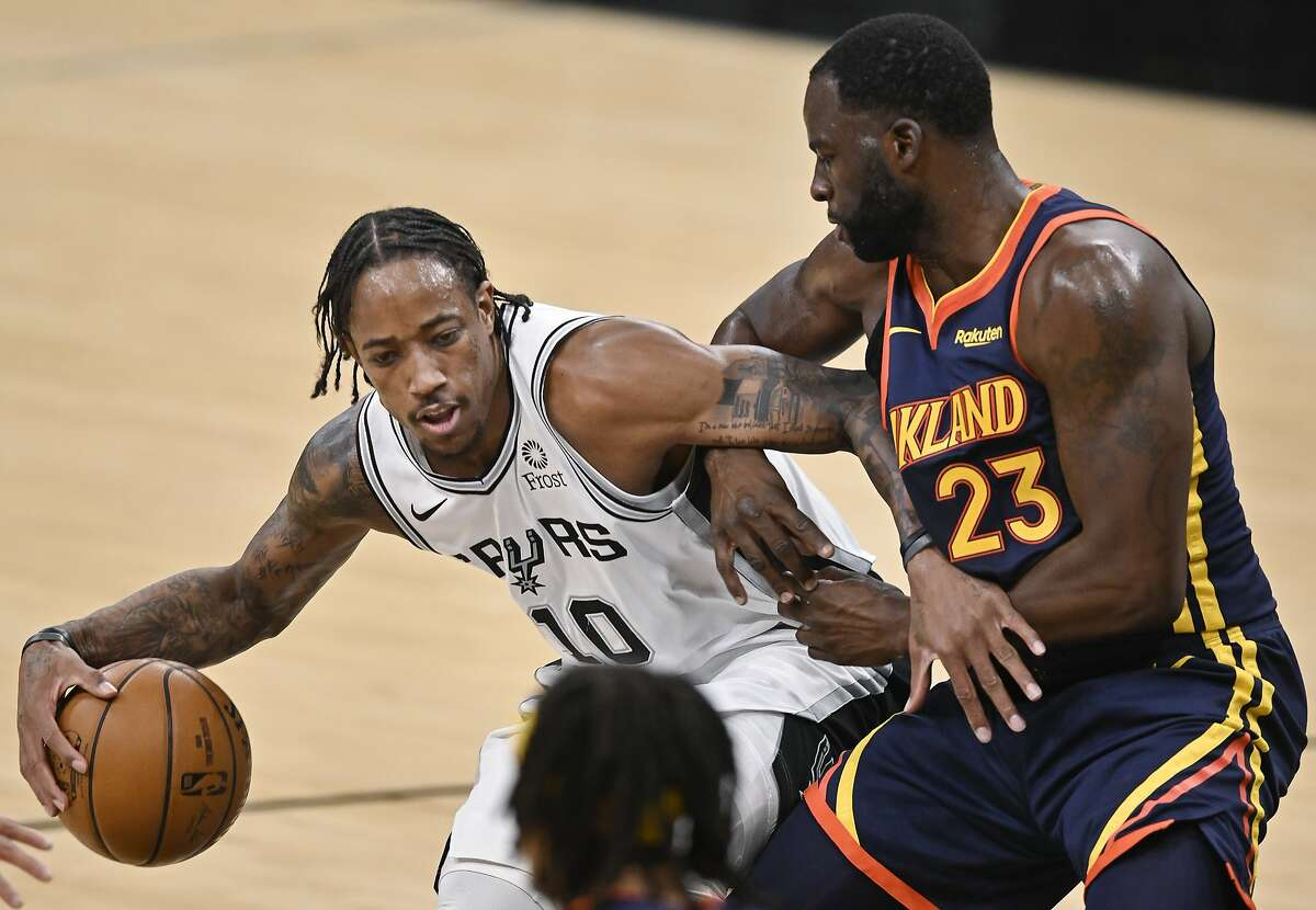 San Antonio Spurs' DeMar DeRozan (10) drives against Golden State Warriors' Draymond Green during the first half of an NBA basketball game, Monday, Feb. 8, 2021, in San Antonio.