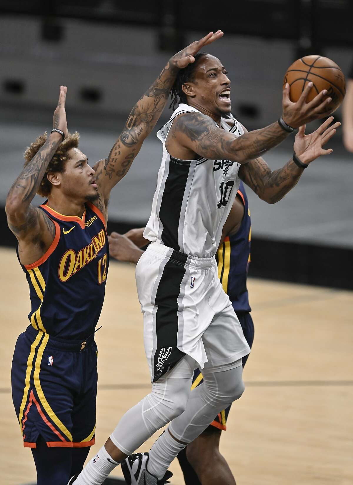 San Antonio Spurs' DeMar DeRozan (10) shoots as he is defended by Golden State Warriors' Kelly Oubre, Jr., left, during the first half of an NBA basketball game, Monday, Feb. 8, 2021, in San Antonio.