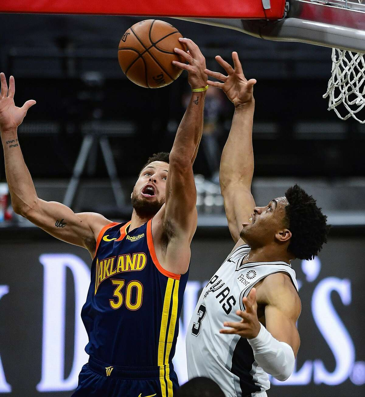 Stephen Curry (30) of the Golden State Warriors battles Keldon Johnson (3) of the San Antonio Spurs for a rebound during first-half NBA action in the AT&T Center on Monday, Feb. 8, 2021.