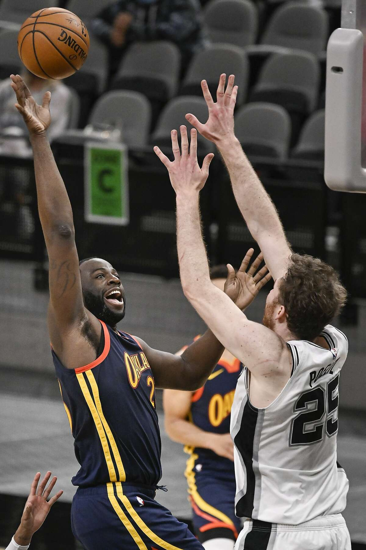 Golden State Warriors' Draymond Green, left, shoots against San Antonio Spurs' Jakob Poeltl during the second half of an NBA basketball game, Monday, Feb. 8, 2021, in San Antonio. (AP Photo/Darren Abate)