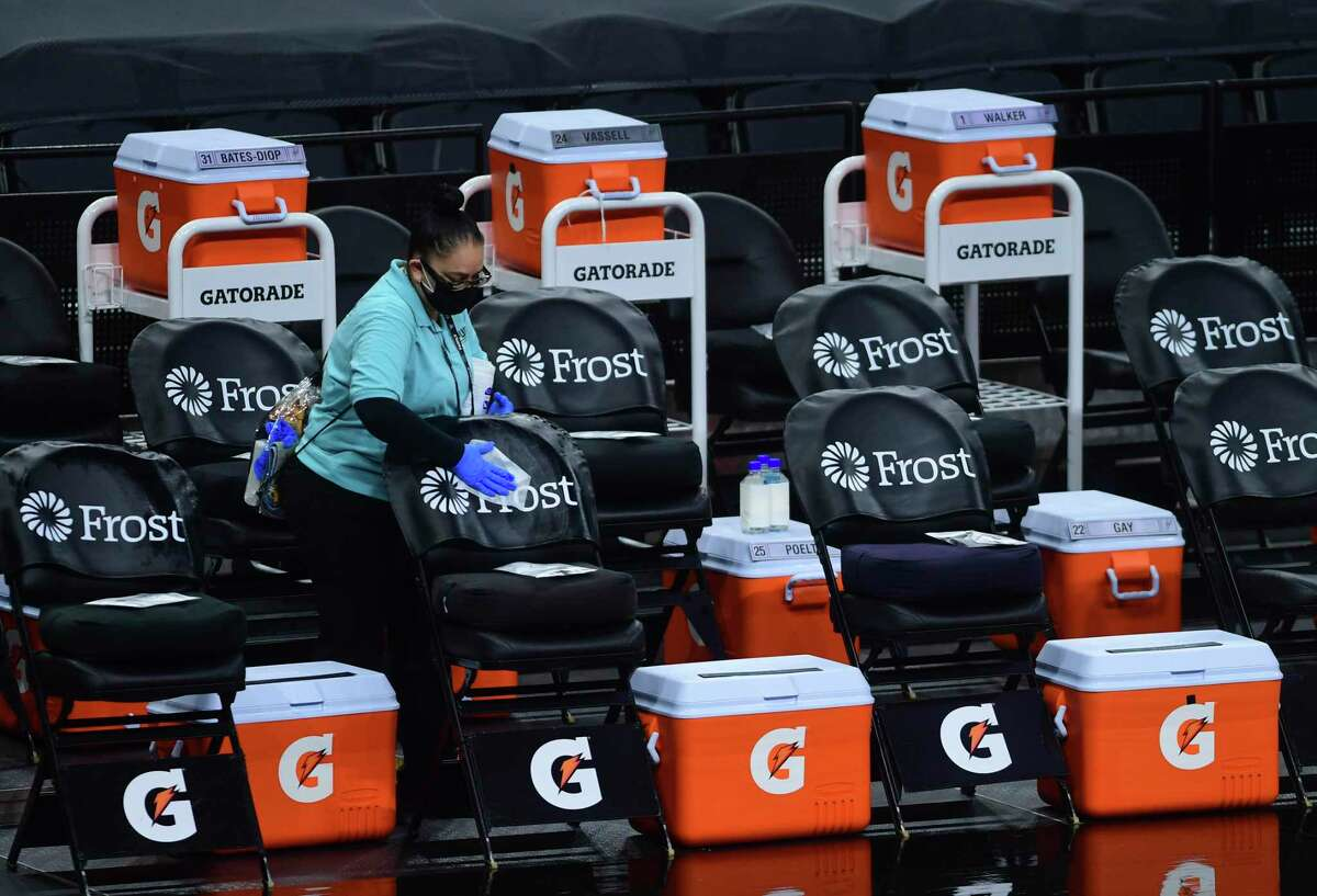 """A member of the """"clean team"""" disinfects the Spurs bench prior to the team's game agains the Golden State Warrior in the AT&T Center on Monday, Feb. 8, 2021."""