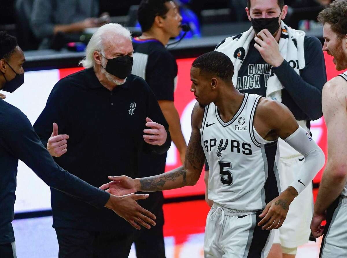 Dejounte Murray (5) of the San Antonio Spurs reacts with teammates and coach Gregg Popovich after scoring on a three-point shot late in the game against the Golden State Warriors during second-half NBA action in the AT&T Center on Monday, Feb. 8, 2021. The Spurs won, 105-100, and Murray had 27 points.