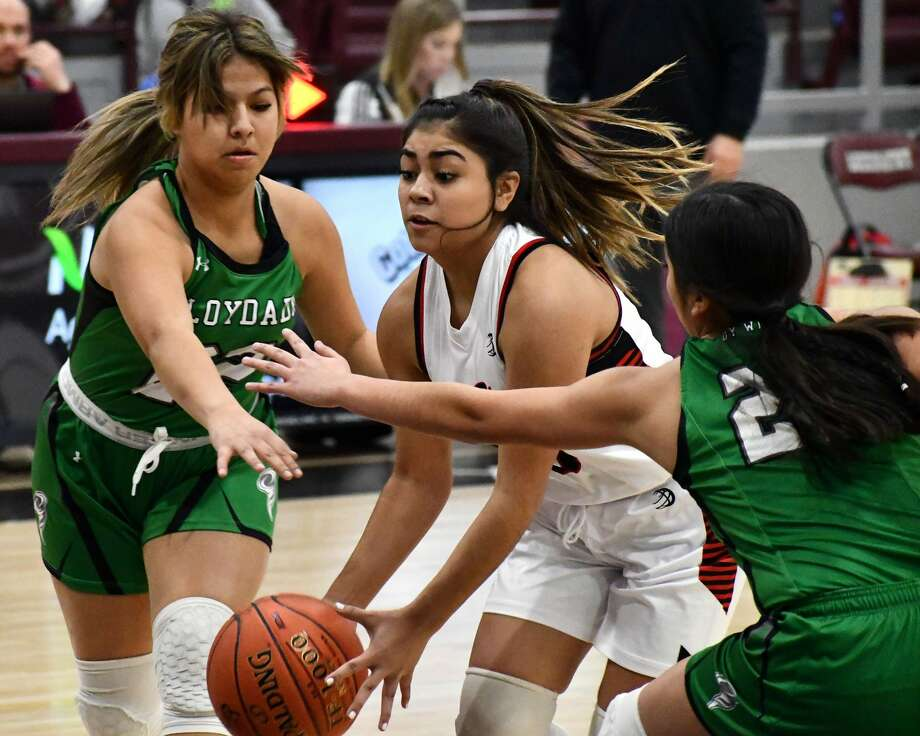 Lockney's Adrianna Villarreal drives in against Floydada defenders Analise Perez (22) and Kailee Sanchez during their District 4-2A tiebreaker girls basketball game on Monday at Abernathy. Photo: Nathan Giese/Planview Herald