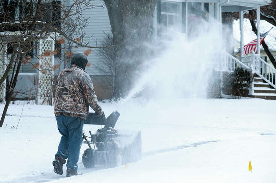 """Steve Sherrill uses his snow blower Monday afternoon, not only to clear the walk in front of his home but to clear most of a block of West Lafayette Avenue just east of North Webster Avenue. """"I'm getting my money's worth with this blower since I only use it once a year,"""" Sherrill said. Photo: Darren Iozia 