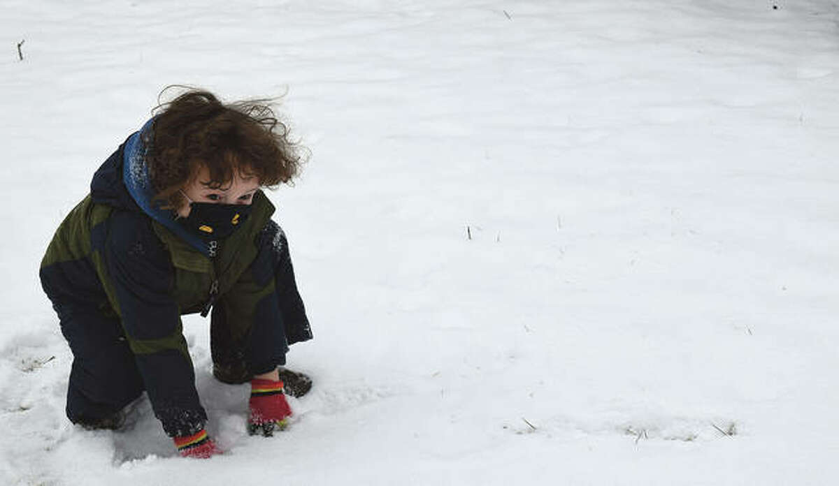 Xander Calaway-Camacho, 4, the son of Jared Calaway and Stacey Camacho of Jacksonville, plays in the snow Monday.