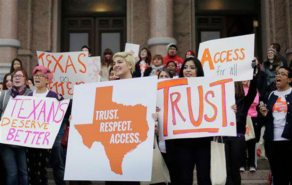 In this Feb. 26, 2015 photo, college students and abortion rights activists hold signs during a rally on the steps of the Texas Capitol, in Austin, Texas.