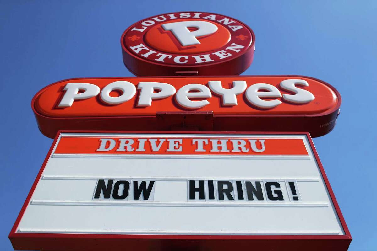 A 'Now Hiring' sign is posted in front of a Popeye's restaurant on February 04, 2021.