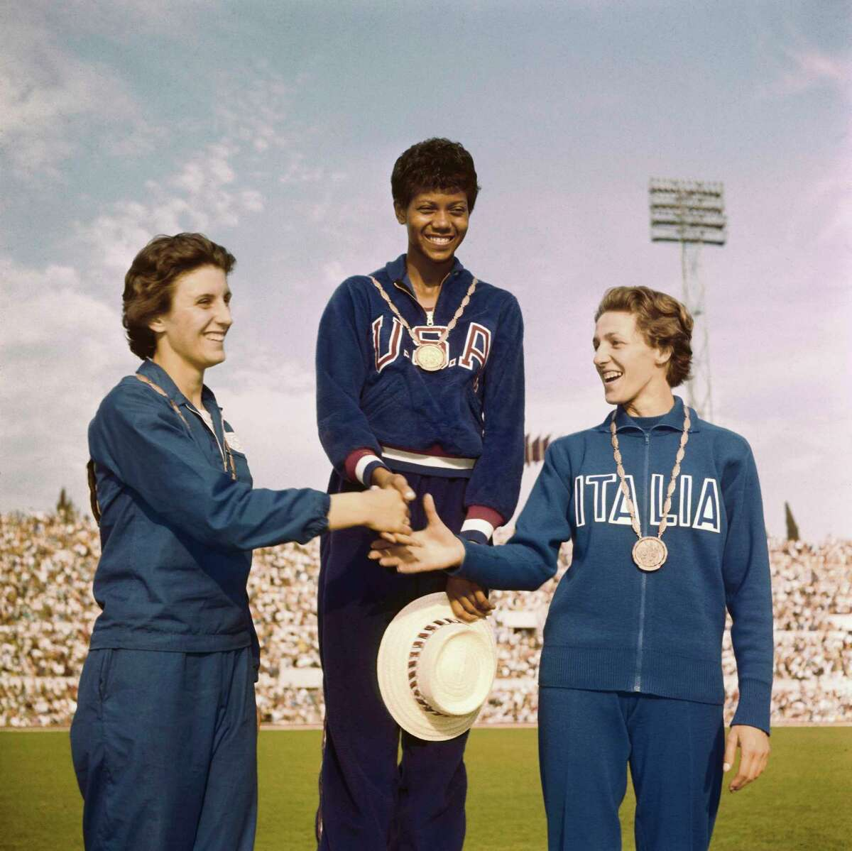 The three winners of the women's 100 meters received their medals, standing on victory podium:first place Wilma Rudolph of U.S.A. (middle), second place Dorothy Hyman of Great Britain (left) and third place Guiseppina Leone of Italy (right).(Courtesy photo/Getty Images)