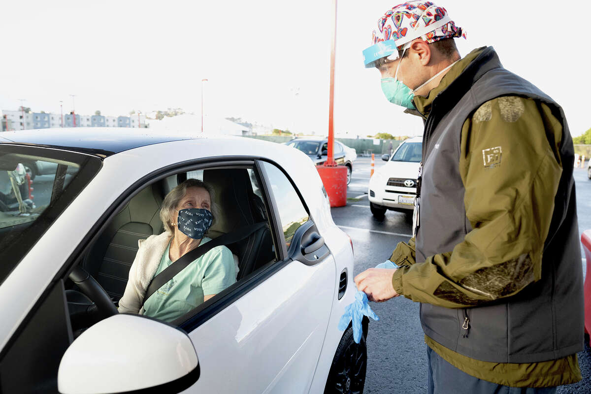 Terry Hill, left, receives her first dose of the Moderna COVID-19 vaccine from Patrick Sorensen, RN, a nurse at UCSF Medical Center, at a vaccination drive-through for SF residents age 75 and older, offered by UCSF and the San Francisco Department of Public Health, in a parking lot at City College San Francisco.