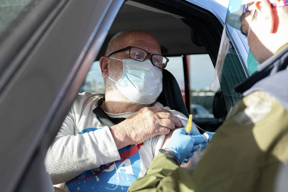Mel Hirschkorn Sr., left, receives his first dose of the Moderna COVID-19 vaccine from Patrick Sorensen, RN, a nurse at UCSF Medical Center, at a vaccination drive-through for SF residents age 75 and older, offered by UCSF and the San Francisco Department of Public Health, in a parking lot at City College San Francisco.