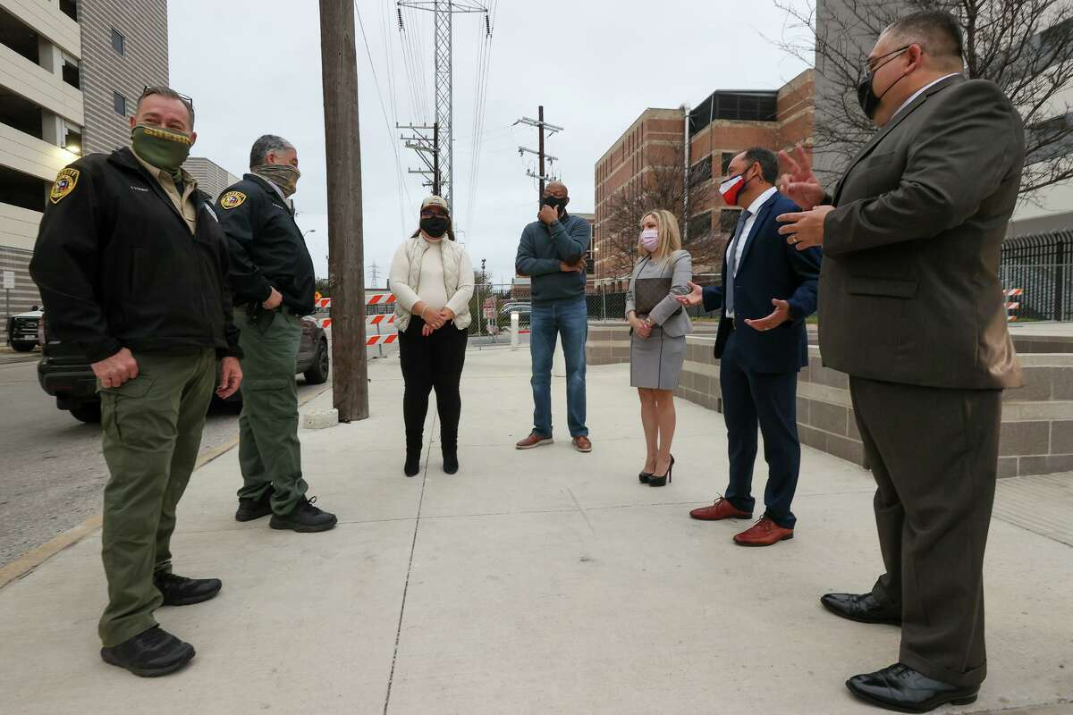 Deputies James Yount and Pete Velasquez, from left, state District Judge Velia Meza, Probation Director Jarvis Anderson and county courts-at-law judges Melissa Vara, Carlo Key and Alfredo Ximenez gather to watch a group of non-violent offenders perform community service outside the Bexar County Adult Detention Center last month.