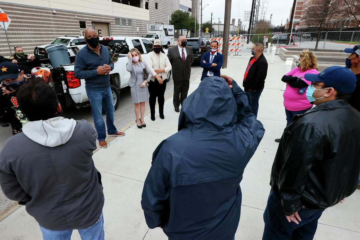 Probation Director Jarvis Anderson, top left, and several local judges, to his left, talk to non-violent offenders preparing to work on landscaping projects outside the Bexar County Adult Detention Center last month as part of their sentences.