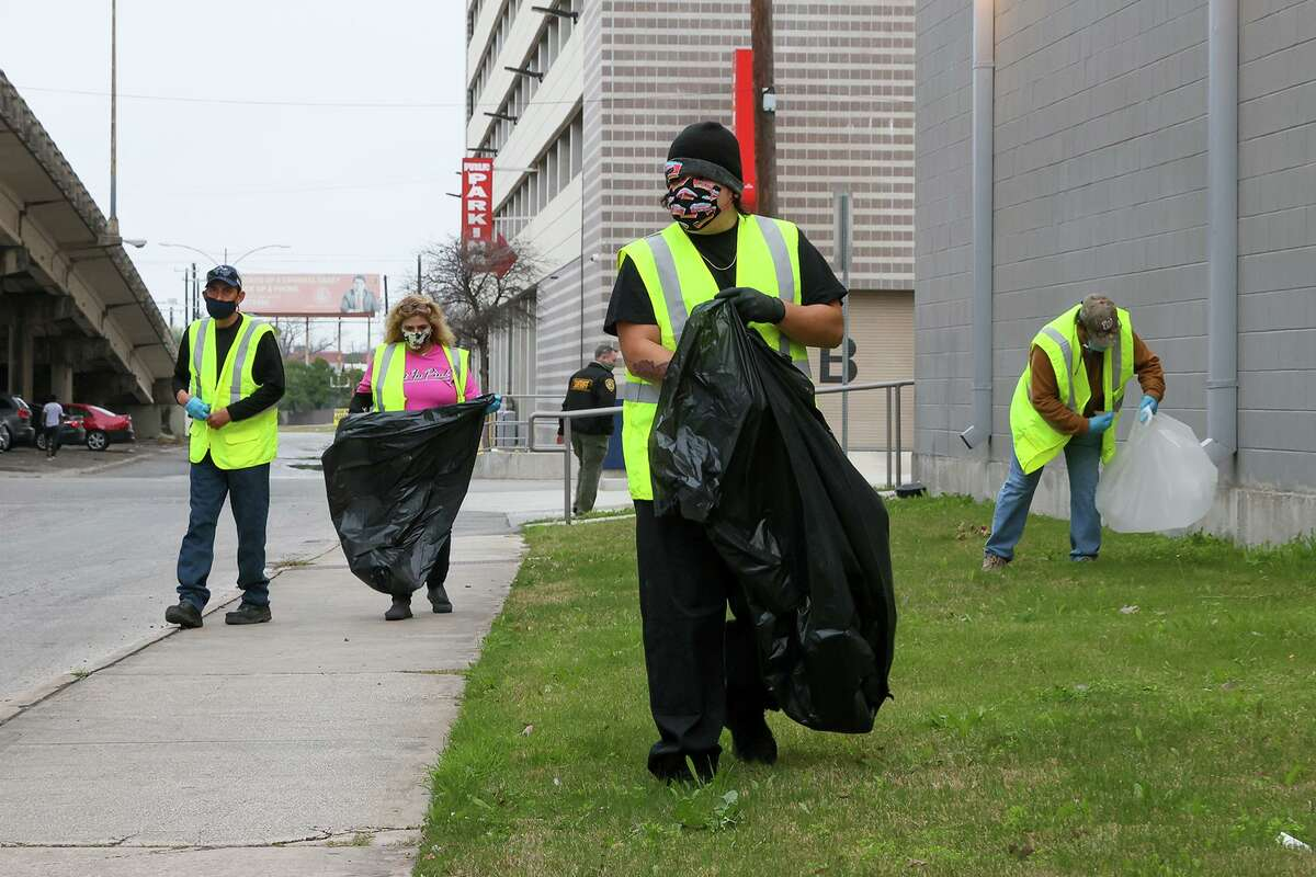 Randy Guia, front, leads a group of non-violent offenders performing community service outside the Bexar County Adult Detention Center last month.